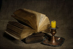 Old books with yellow candle on canvas background Stock Photos