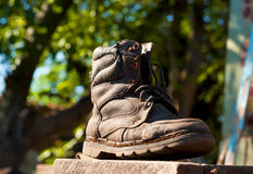 Old boot. An old dirty  boot  on a dark background is lighted up by a sunlight Stock Image