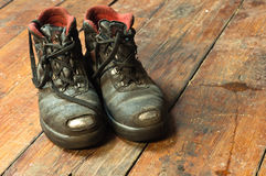 Old Boot. Old dirty boot on wooden boards with blurry back stock images