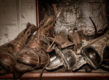 Old Boots and Ice skates. Vintage leather working boots and ice skates on shelf in display of rural bygones in Alford, Lincolnshire, Uk in shades of brown stock image