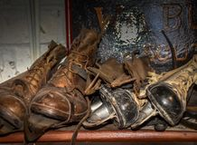 Old Boots and Ice skates. Vintage leather working boots and ice skates on shelf in display of rural bygones in Alford, Lincolnshire, Uk in shades of brown stock photo
