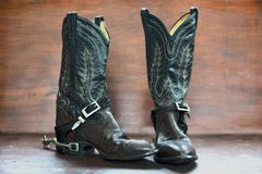 Old Boots and Spurs over a wooden background. Pair of old cowboy boots with spurs on a wooden background royalty free stock photos