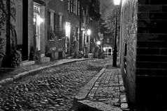 Old boston street. Black and white image of an old 19th Century cobble stone road in Boston Massachusetts, lit only by the gas lamps revealing the shuttered Royalty Free Stock Image