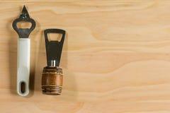 Old bottle openers. Overhead shot image of old bottle openers on wooden background stock photo
