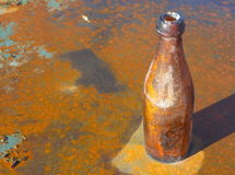 Old bottle. On a rusty plate Stock Photos