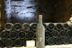 Old bottle of wine in the cellar of the winery Ancient wine bott. Old bottle of wine in the cellar of the winery Stock Images