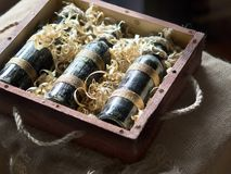 Old bottles of wine in wood shaving stock photography