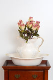 Old bowl and jug on a stand with fake roses Stock Photo