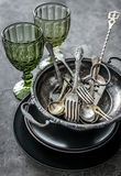 Old bowls, spoons and silverware, heavy greenish glasses Stock Photo