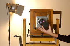 Old Box Camera. A photographer removing lens of an old wooden box camera Stock Image