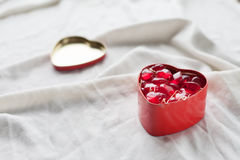Old box in heart shape on white background, on white cloth, in box red sweet jelly beans, Valentine`s day, women`s day, gifts Royalty Free Stock Photo