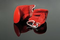Old boxing gloves. Old red boxing gloves on black reflective background Royalty Free Stock Photo