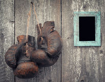 Old boxing gloves and frame for photo. Old boxing gloves and photo frame on a wooden wall Stock Photos