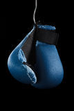 Old boxing gloves hang on nail black background Royalty Free Stock Images