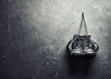 Old boxing gloves hang on nail on texture wall. With copy space for text. Retirement concept Royalty Free Stock Image