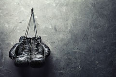 Old boxing gloves hang on nail on texture wall stock images