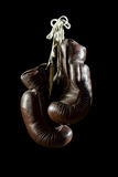 Old Boxing Gloves, hanging, on black Background Stock Images