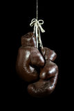 Old Boxing Gloves, hanging, on black Background royalty free stock images