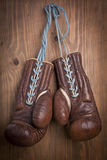 Old boxing gloves with a lace over  wooden wall Royalty Free Stock Photos