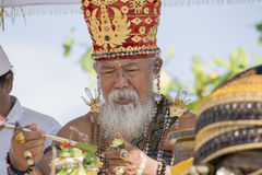 Old Brahmin conducts religious ritual on the beach Ketewel. Bali, Indonesia Stock Image