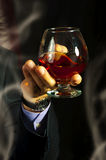 Old Brandy Glass at male hand. And smoking on black background. men's club Stock Images
