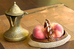 Old brass arabian style coffee pot and ceramic vase with peaches. On a table Royalty Free Stock Image
