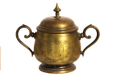 An old brass or bronze metal sugar bowl with a lid and ornament. Metal punctles with scratches and patina. Royalty Free Stock Photo