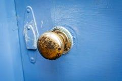 Old brass door handle on a painted blue door. Antique brass door handle shot against a crudely painted blue door royalty free stock image