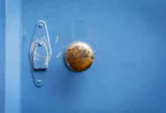 Old brass door handle on a painted blue door. Vintage brass door handle shot against a blue painted wooden door Royalty Free Stock Photography