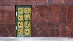 Old brass door on marble wall. Background stock photography