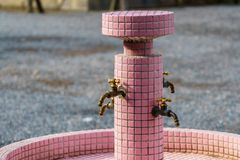 Brass Faucets in Garden. Old Brass Faucets on Pink mosaic pillar in Garden stock photography