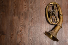 Old brass horn. On wooden background stock image