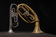 Old brass instrument and horn stand on a table Stock Images