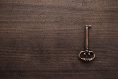Old brass key on wooden table Stock Image