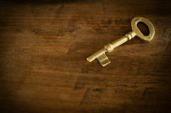 Old brass keys placed on a wooden floor low key light. Royalty Free Stock Photography