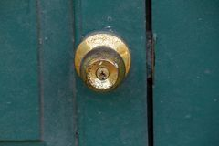 Old brass knobs on the green door. Used to close or open the door stock images