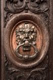 Old brass knocker. Depicting a mask on a wooden door stock image