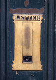 Old brass letterbox. Old brass letter box in a blue door with peeling paint Royalty Free Stock Photos