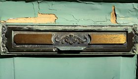 Old brass mail letter box on front door stock images