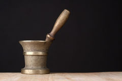 Old brass mortar. With a pestle on a wooden table royalty free stock images