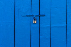 Old Brass Padlock on Wooden Blue Gate. Vivid color Royalty Free Stock Image