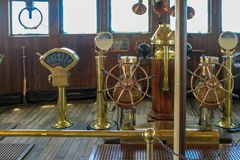 Old brass ships wheels and navigation instruments. In the control room or bridge on a historic ship stock images