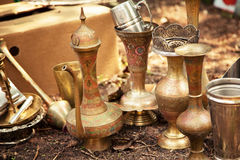 Antique Indian handicraft etched vases and surahi jug at a flea market. Old brass tableware collectibles at a garage sale Stock Photos