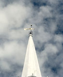 Old brass weather vane on top of a white cone-shaped tower Stock Photo