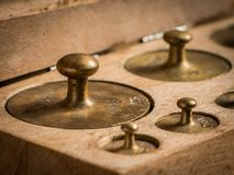 Old brass weights for a kitchen scale. In a wooden box stock images