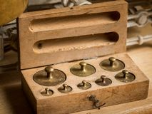 Old brass weights for a kitchen scale. In a wooden box stock image