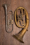 Old brass wind instrument and horn  on a wooden background Royalty Free Stock Image
