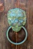 Old brazen lion head door knocker on a wooden door. Mdina, Malta Stock Photo