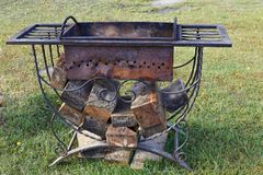 Old brazier with firewood. On  lawn Royalty Free Stock Photos