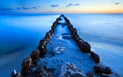 Old breakwater in North sea in dusk Stock Photos